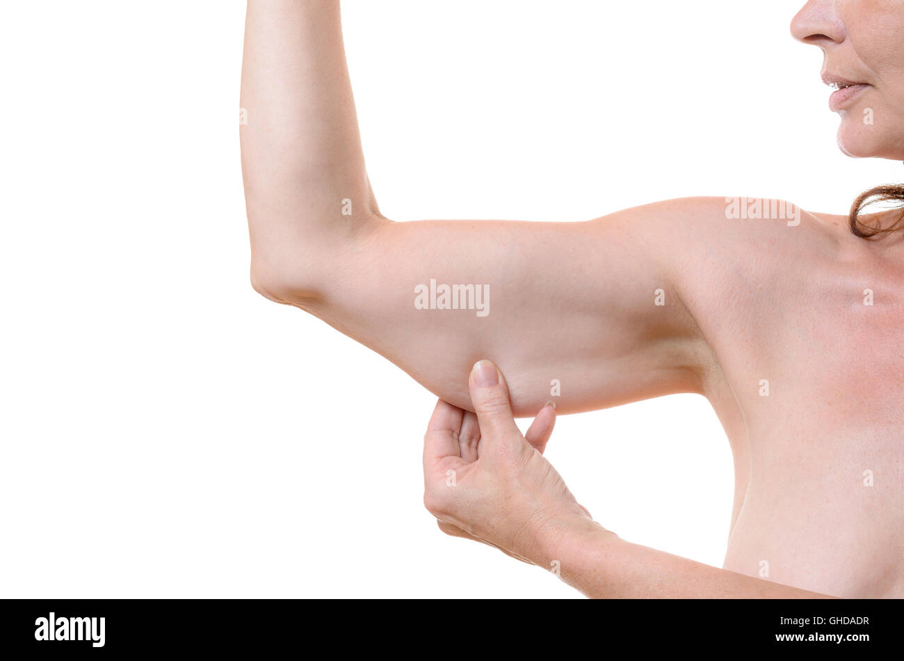 Middle-aged woman grasping her underarm flesh between her fingers showing the slackening of the tissue due to ageing, - Stock Image
