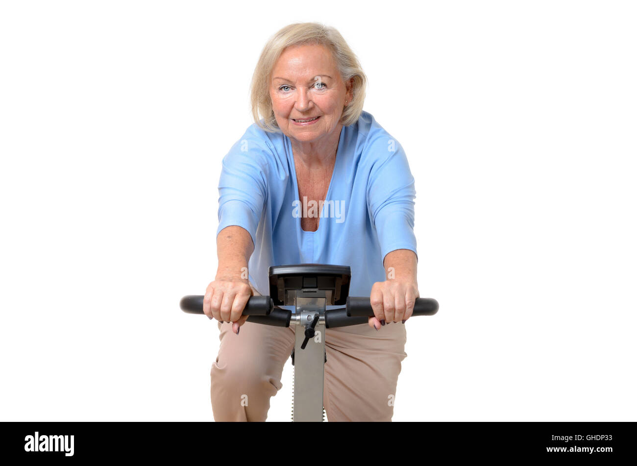 Smiling elderly woman riding an exercise bicycle at a gym or home