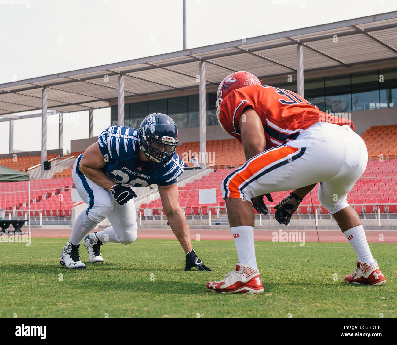 American football players face off during a training session. - Stock Image