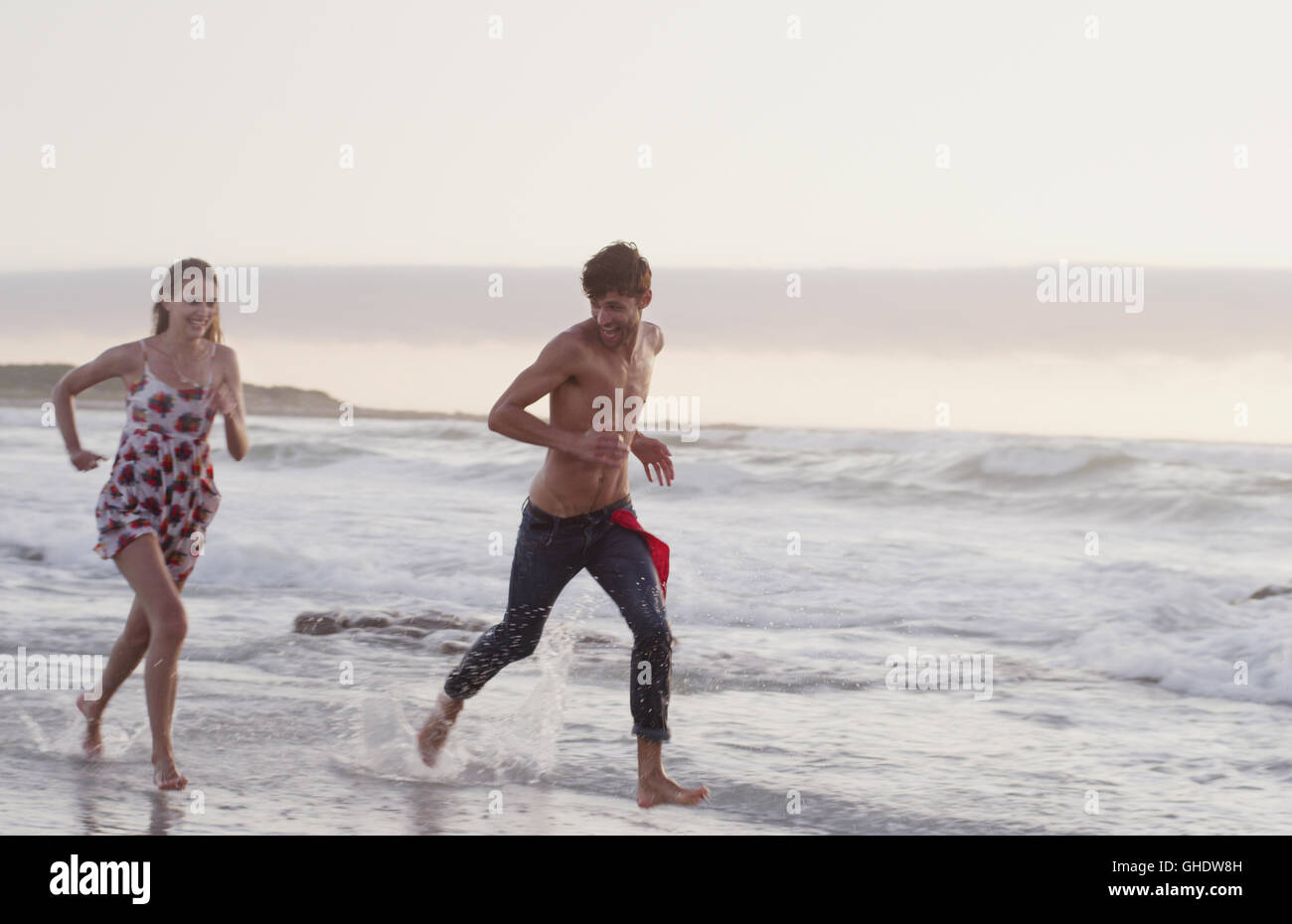 Young couple running in ocean surf Stock Photo