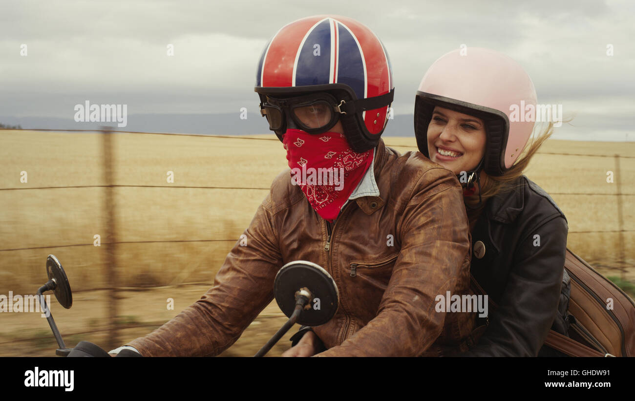 Young couple riding motorcycle in rural countryside Stock Photo