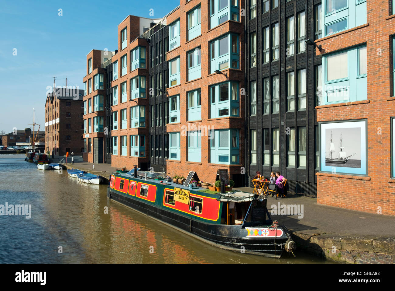 Canal boat cafe moored alongside new build apartments and shops in spring sunshine at Gloucester Docks, Gloucester, UK Stock Photo