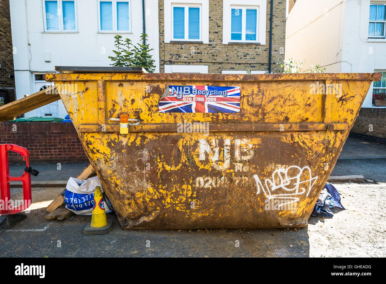 Yellow Skip outside a house renovation in South East London, Southwark, England, UK - Stock Image