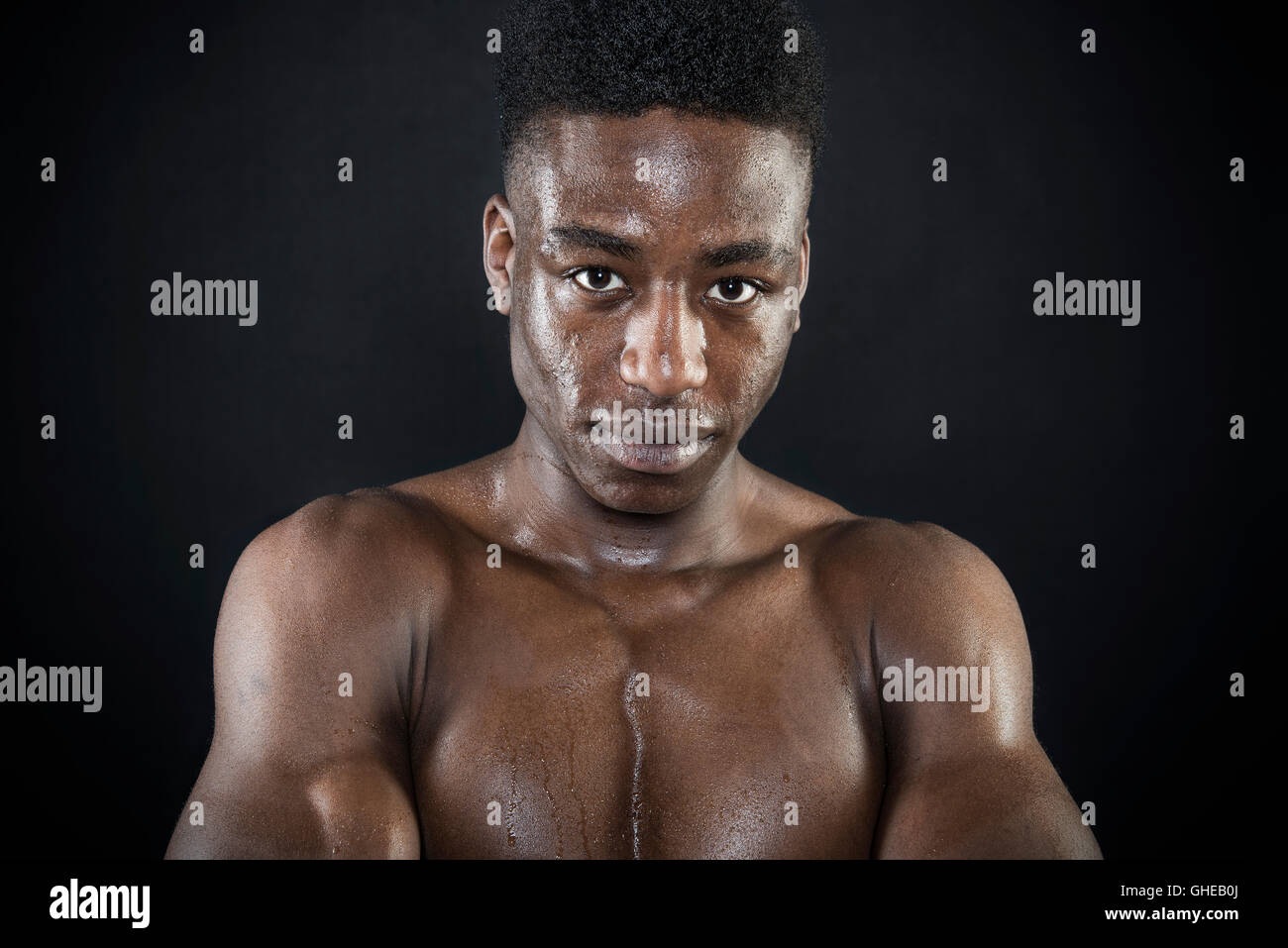 Sportsman athlete sweating wet face portrait after exercise arms folded intense look isolated black - Stock Image