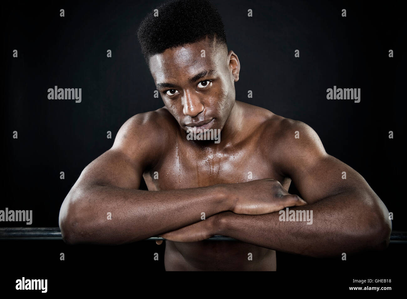 Sportsman athlete sweating wet face portrait after exercise arms folded leaning on bar intense look isolated black - Stock Image