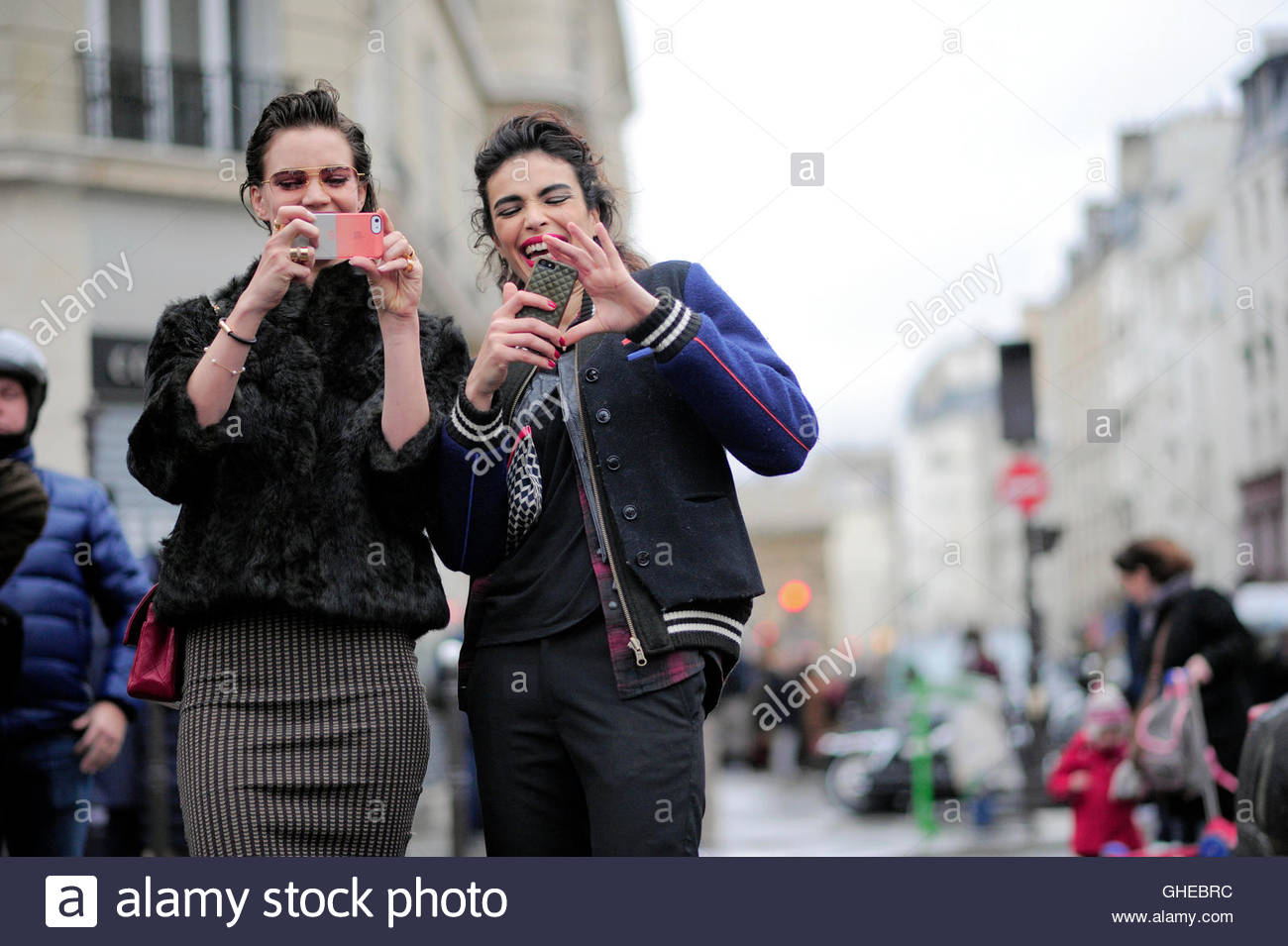 Women taking photos with their phones on Rue St Martin during Paris Fashion Week. - Stock Image