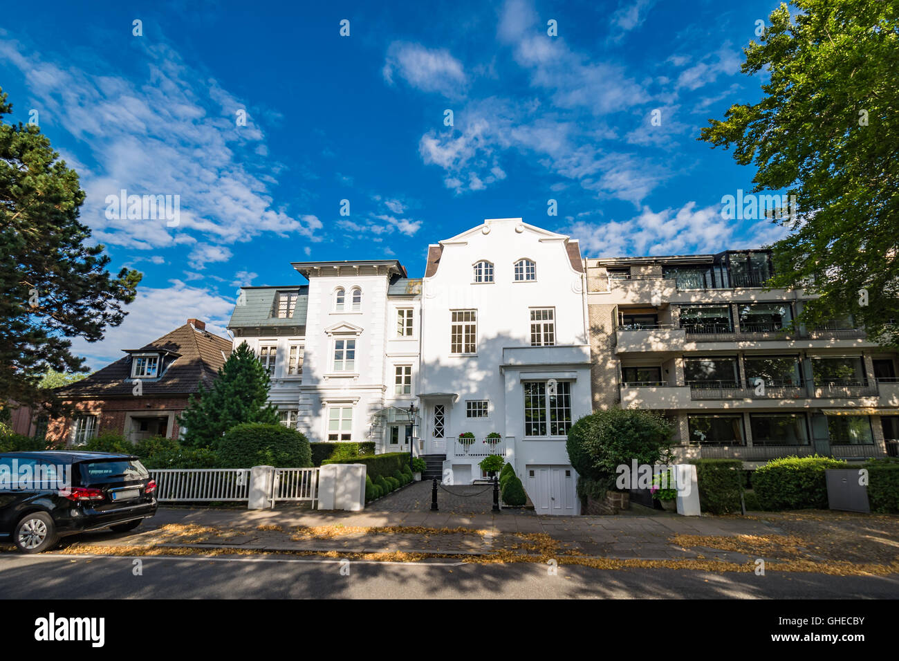 Luxury old mansions in Winterhude neighbourhood against blue sky on a sunny summer day, image for real estate agent - Stock Image