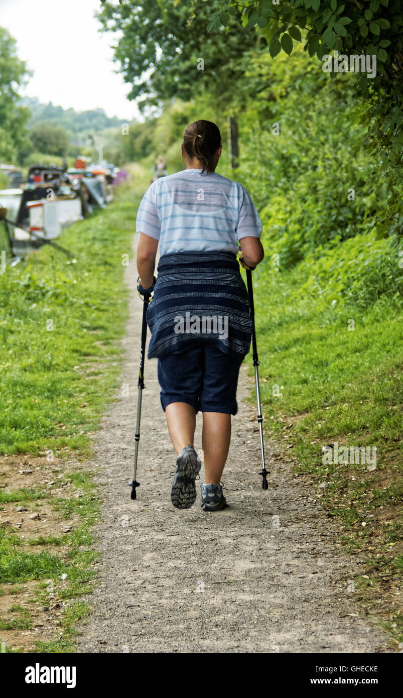 Walker using walking poles on towpath by canal - Stock Image