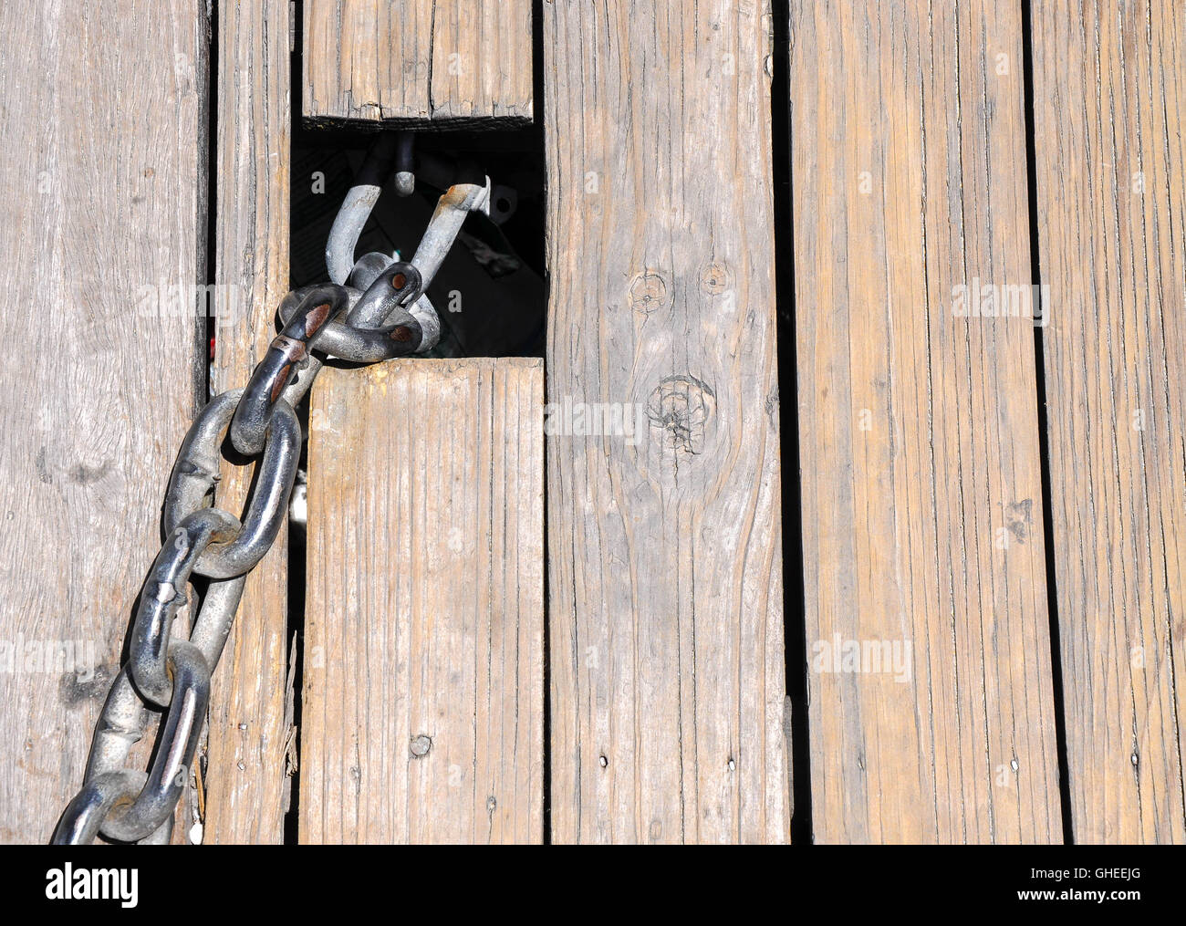 Abstract closeup of weathered wooden planks and tense metal chain link exiting square cutout. - Stock Image