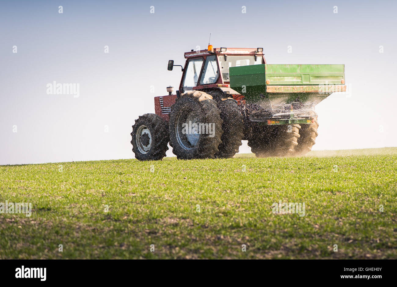 Tractor and fertilizer spreader in field - Stock Image