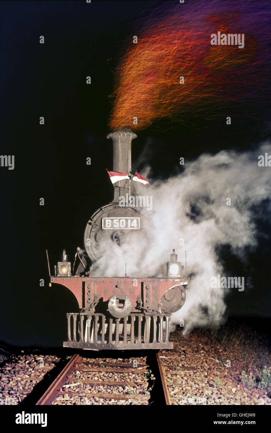The fluttering flags celebrate Independence Day in August as an Indonesia State Railway B50 Class 2-4-0 heads an - Stock Image