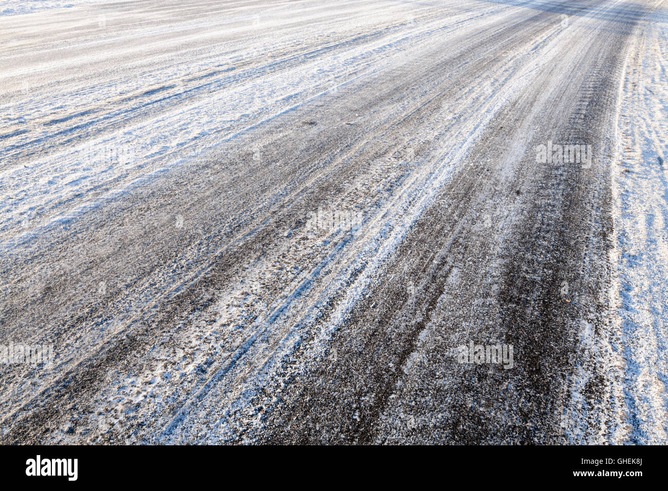 Tyre tracks left in snow and ice on road in Winter, England, UK - Stock Image