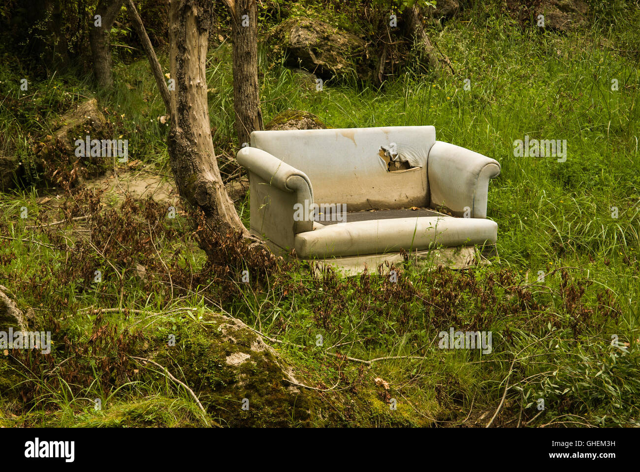 Old sofa dumped in a forest an example of fly tipping or illegal dumping - Stock Image