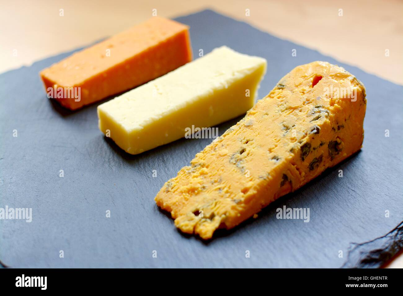 Three cheese selection served on black slate - Stock Image