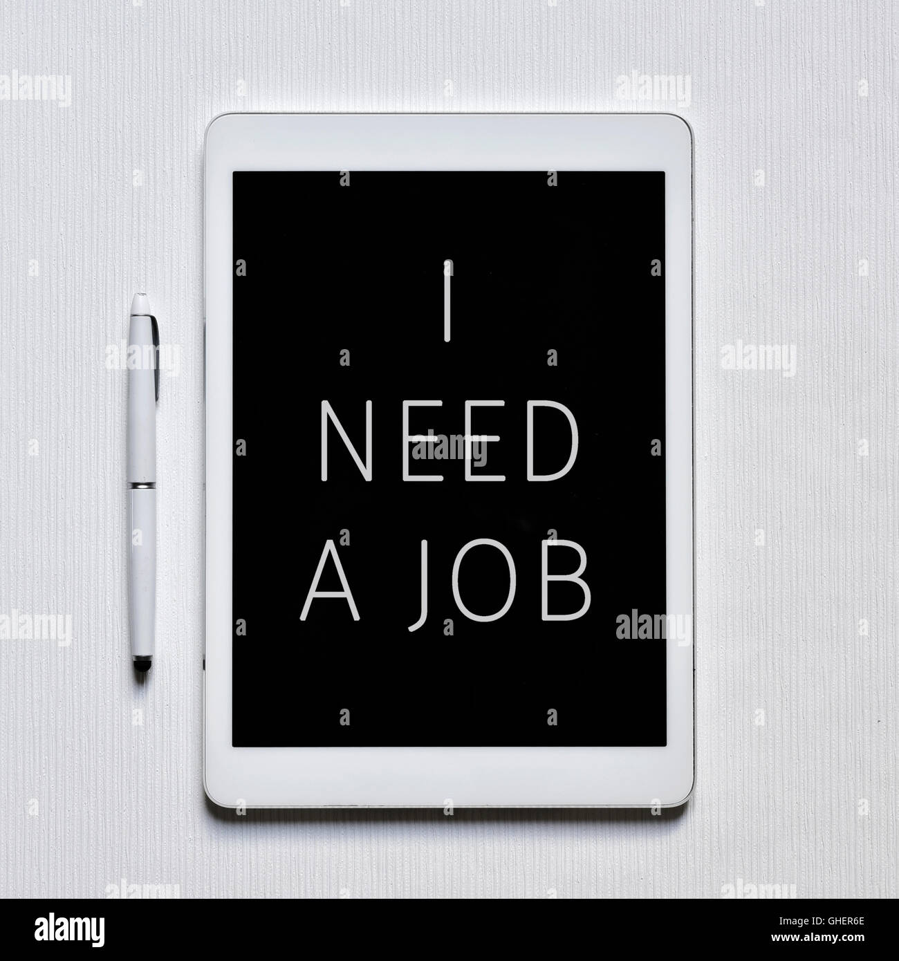 high-angle shot of a tablet computer with the text I need a job in its screen and a digital pen on a white surface - Stock Image