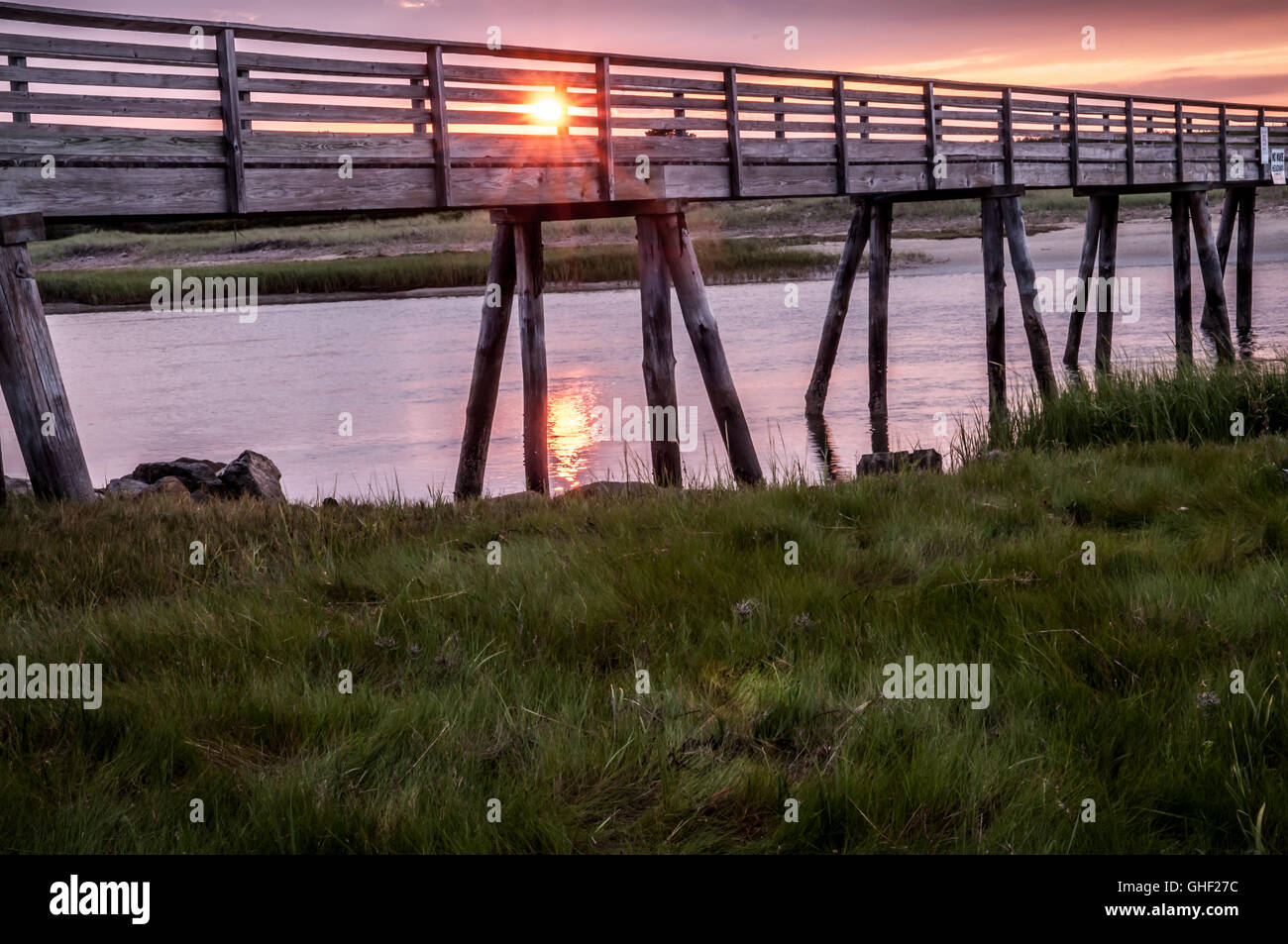 The Sun comes up on the other side of the bridge giving off its glow. It looks like it is making its way across - Stock Image