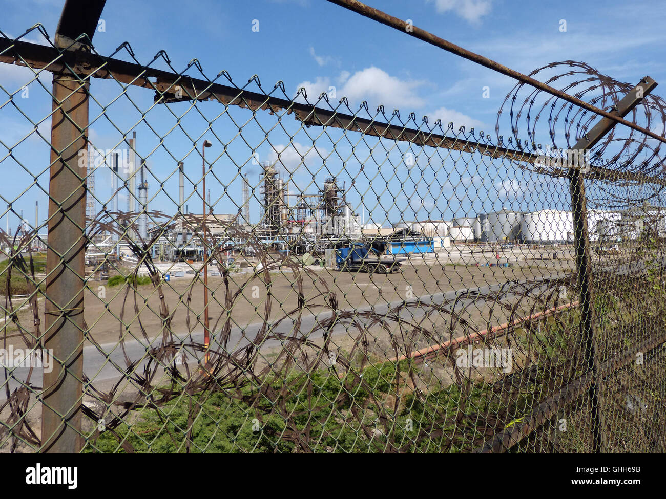Willemstad, Netherlands. 09th Aug, 2016. A look through the metal fence at the Isla refinery on the island of Curacao - Stock Image