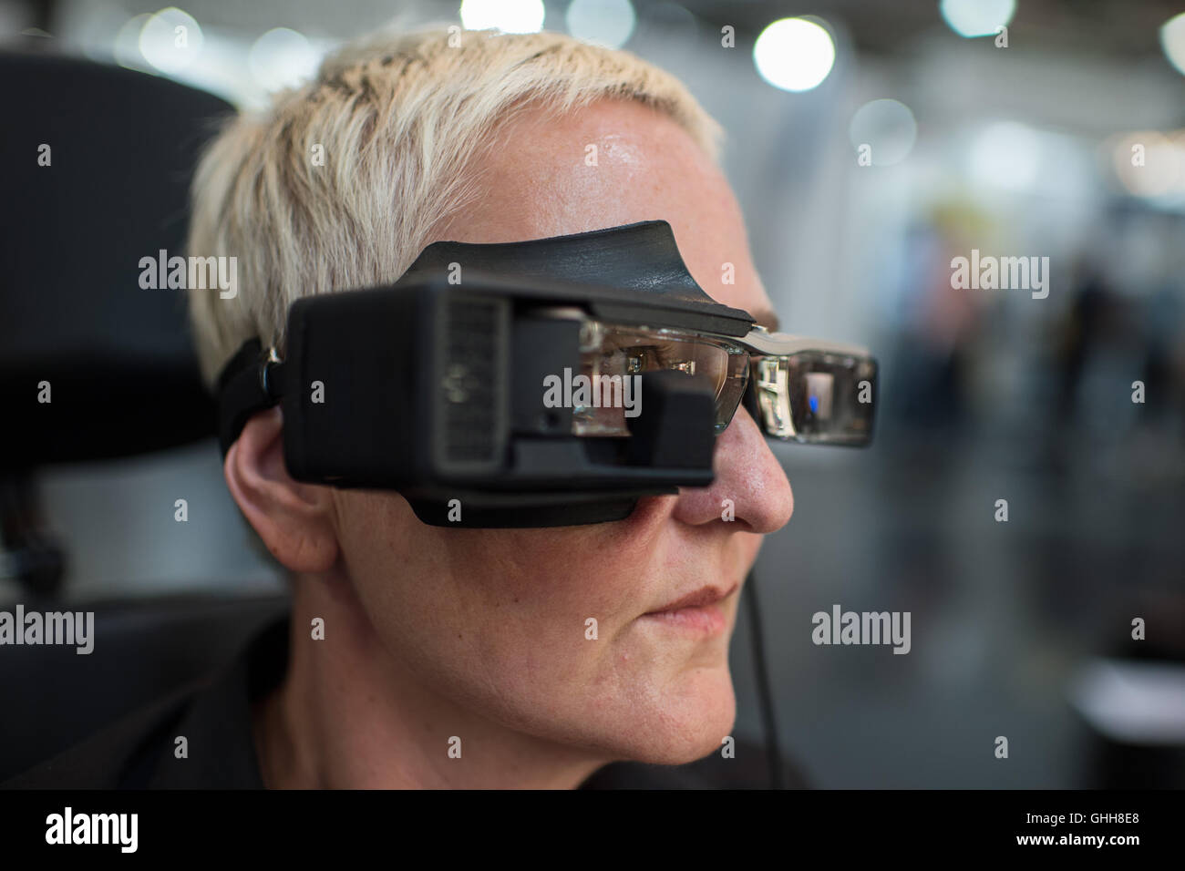 Duesseldorf, Germany. 28th Sep, 2016. A woman wearing the so-called 'Eye Speak' glasses during the opening of the international care fair 'Rheacare' in Duesseldorf, Germany, 28 September 2016. The glasses are equipped with a screen and a virtual keyboard. An inbuild camera recognises the eye movement of the person wearing the glasses, allowing the selection of letters on the monitor. The glasses are said to be a communication system for people with extremely limited movement and communication. The fair runs until 1 October 2016. PHOTO: WOLFRAM KASTL/dpa/Alamy Live News Stock Photo
