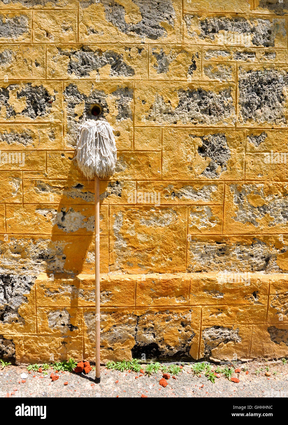 White industrial mop leaning against an limestone brick building exterior with shadow. - Stock Image