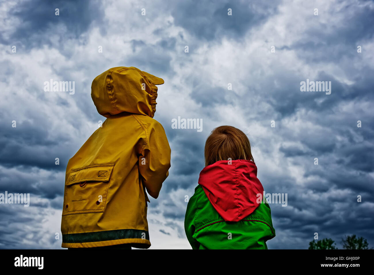 Two children stood together looking anxiously at an approaching storm - Stock Image