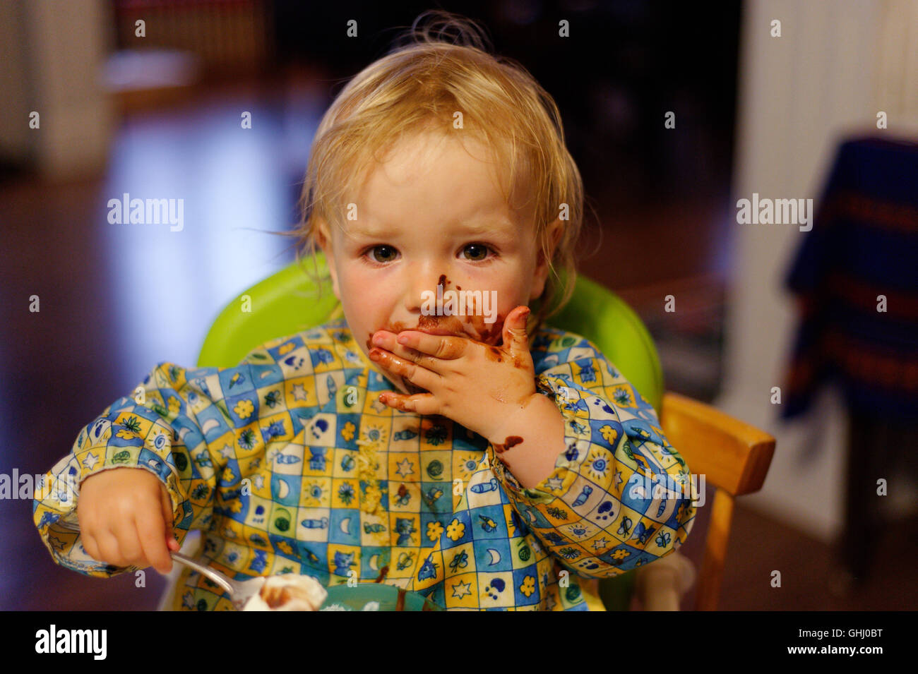 A little girl (2 yrs old) eating chocolate cake - Stock Image