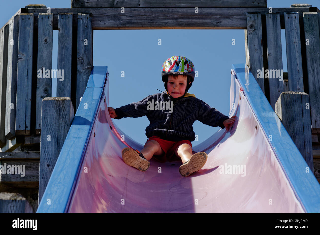 A scared boy (4 yrs old) sat looking down a long slide - Stock Image