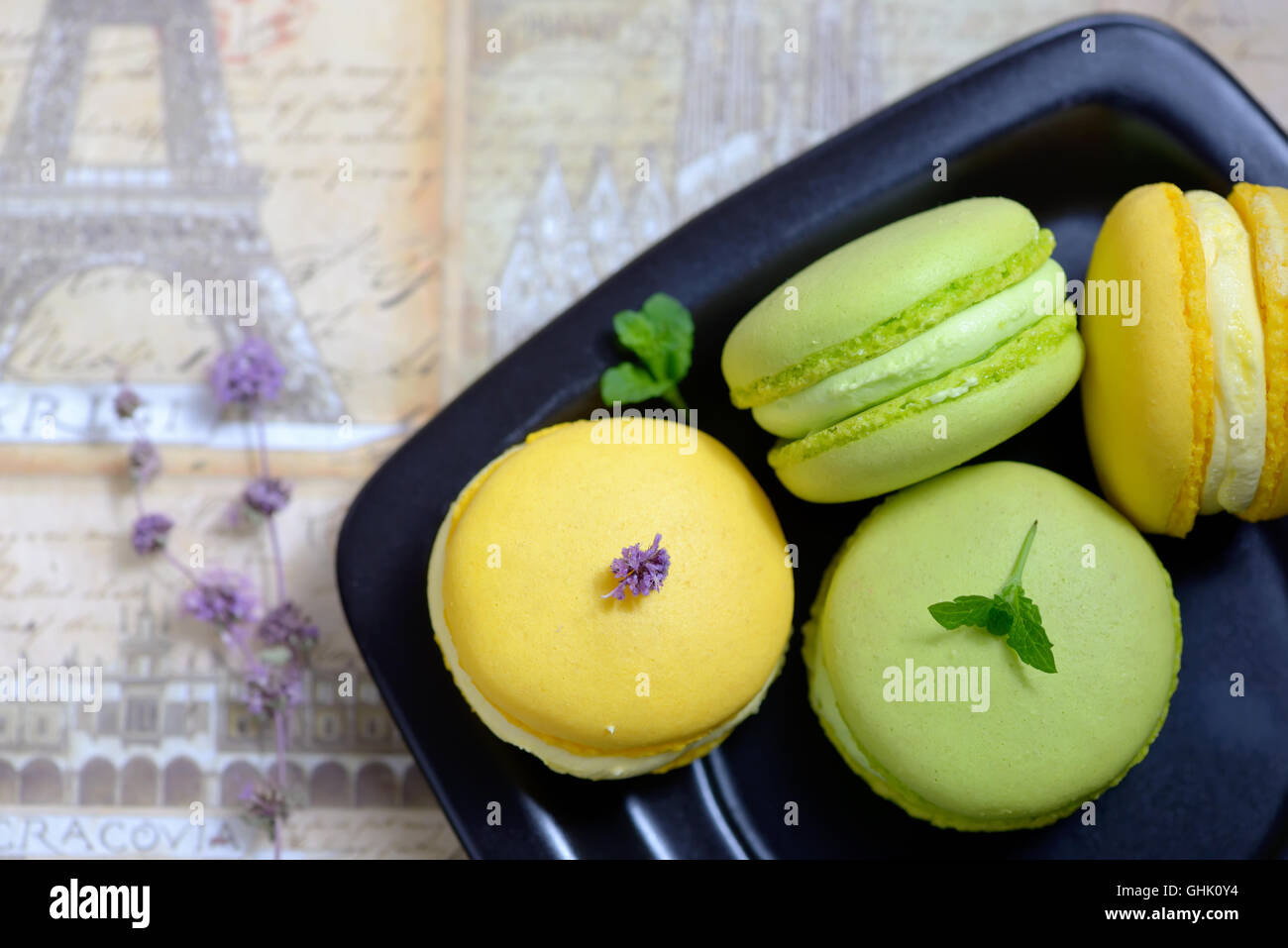 Lemon and mint flavor french macarons on black plate - Stock Image