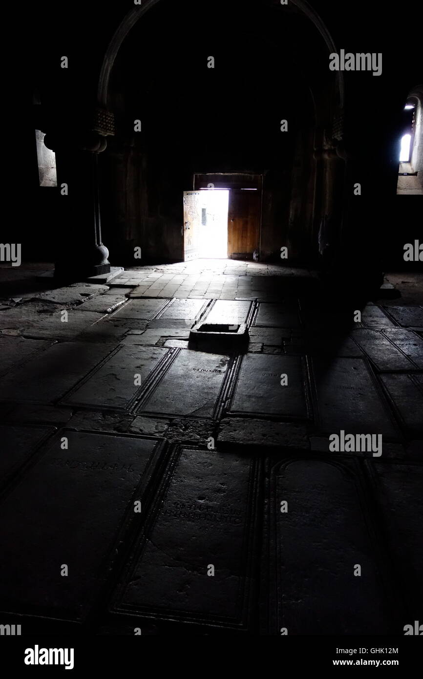 Haghpat N Armenia monastic church Holy Cross with embellished basalt grave slabs on floor subtly lit from natural - Stock Image