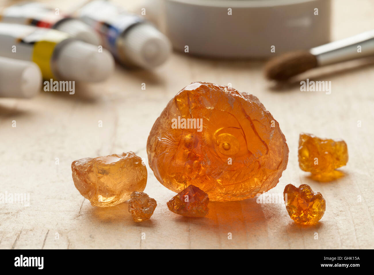Pieces of Gum arabic with paint and paintbrushes in the background - Stock Image