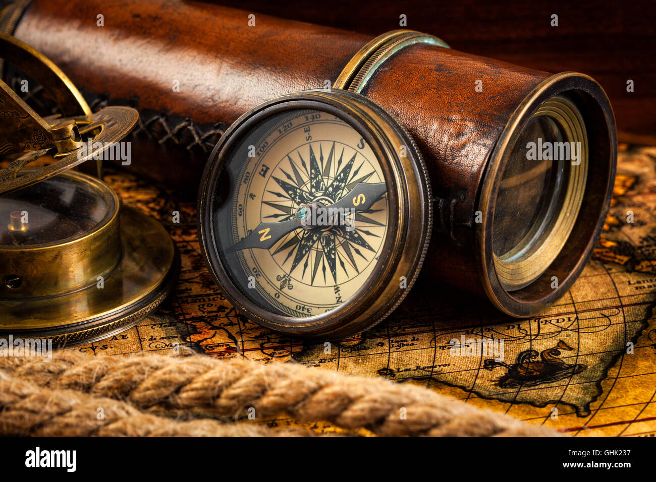 Old vintage compass and navigation instruments on ancient map - Stock Image