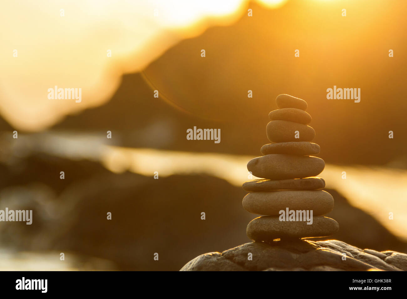 Stones Balance in sunrise at sea in summer - Stock Image