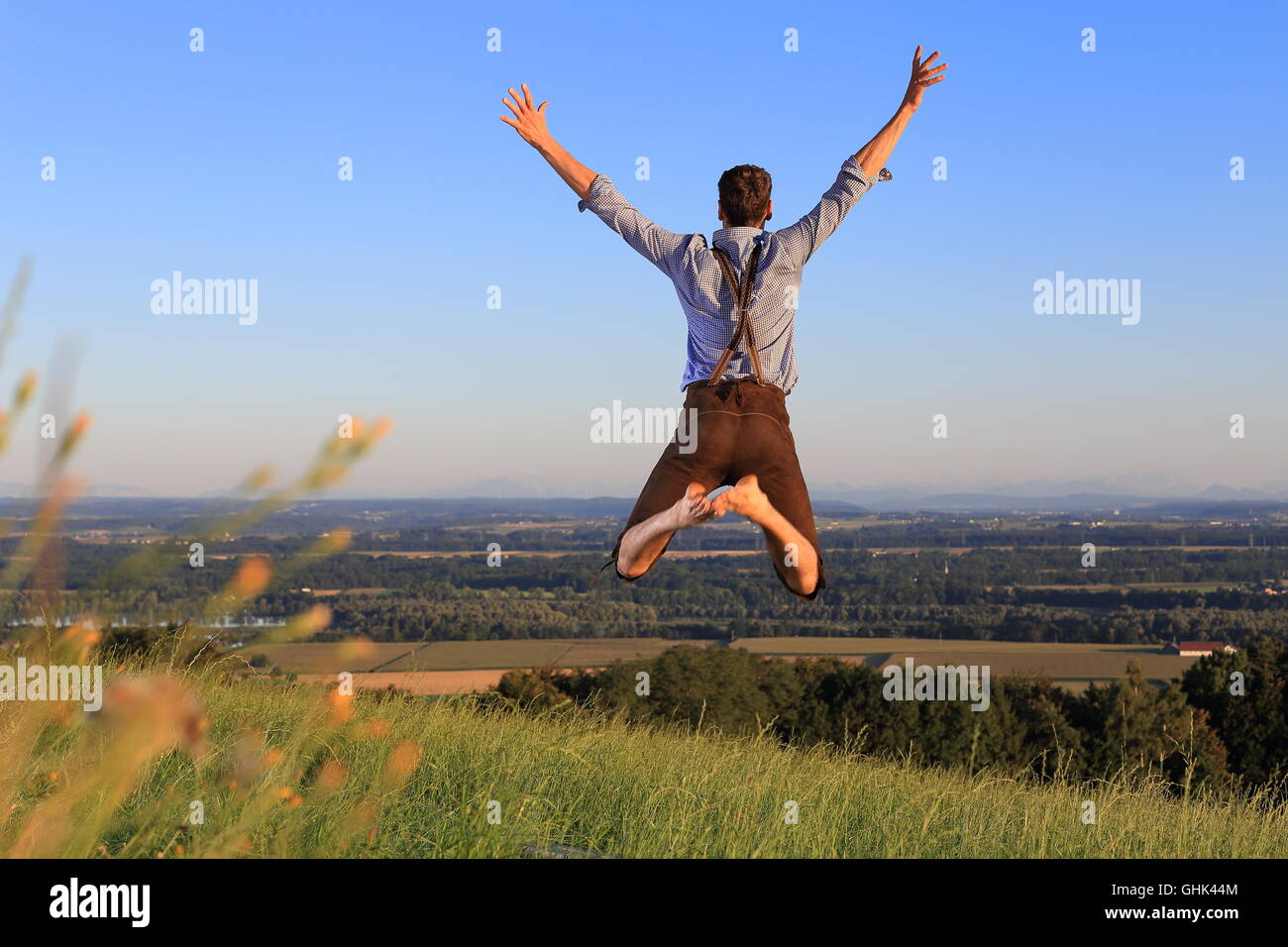 A German Man in Bavarian dress jumping happily on lawn - Stock Image