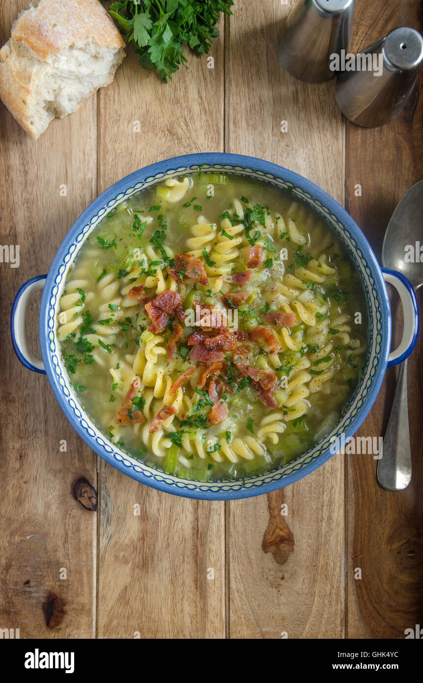 Leek and pasta soup topped with bacon - Stock Image