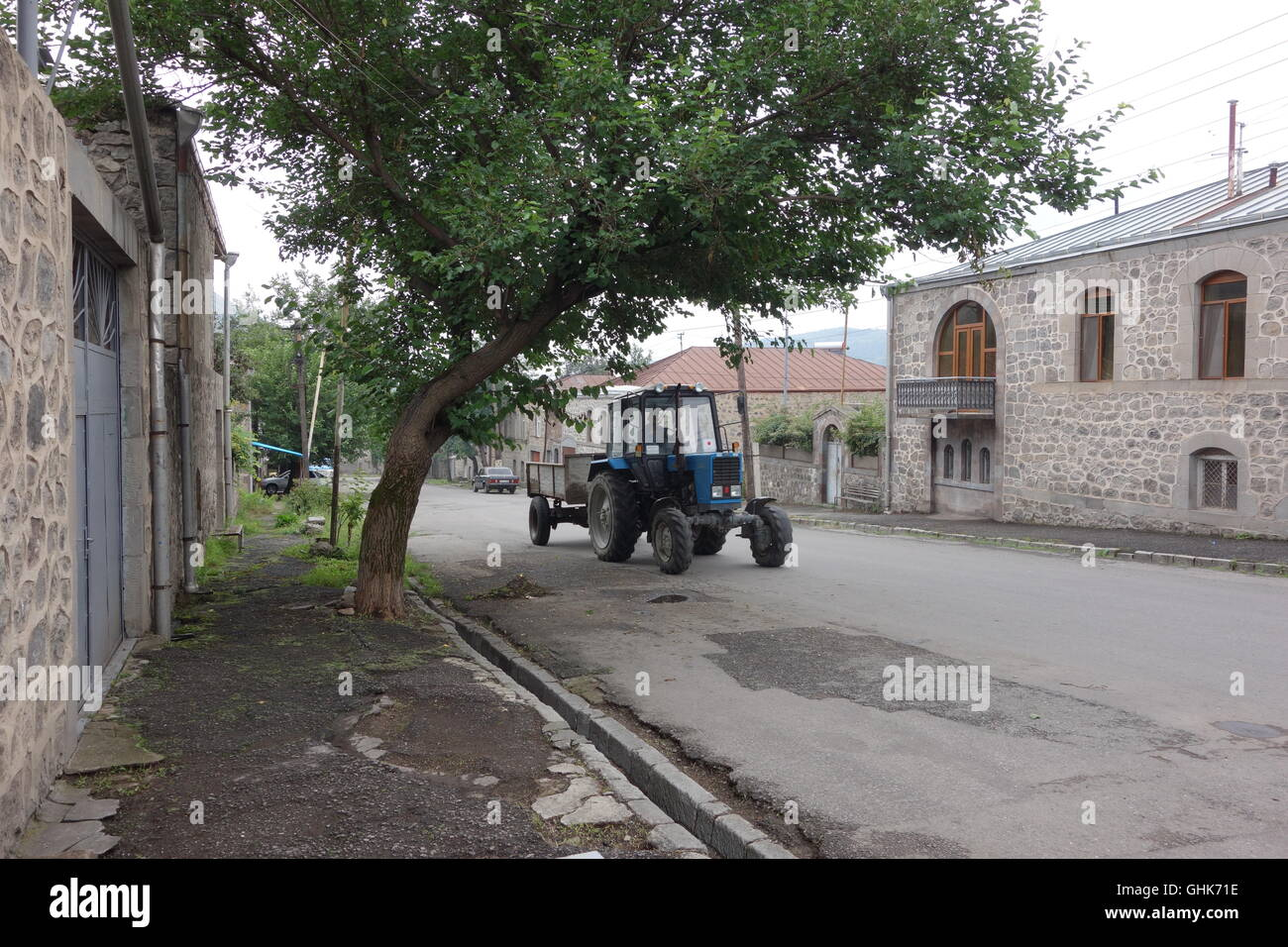 tractor in main street Goris Armenia provincial town to south of country all houses stone built - Stock Image