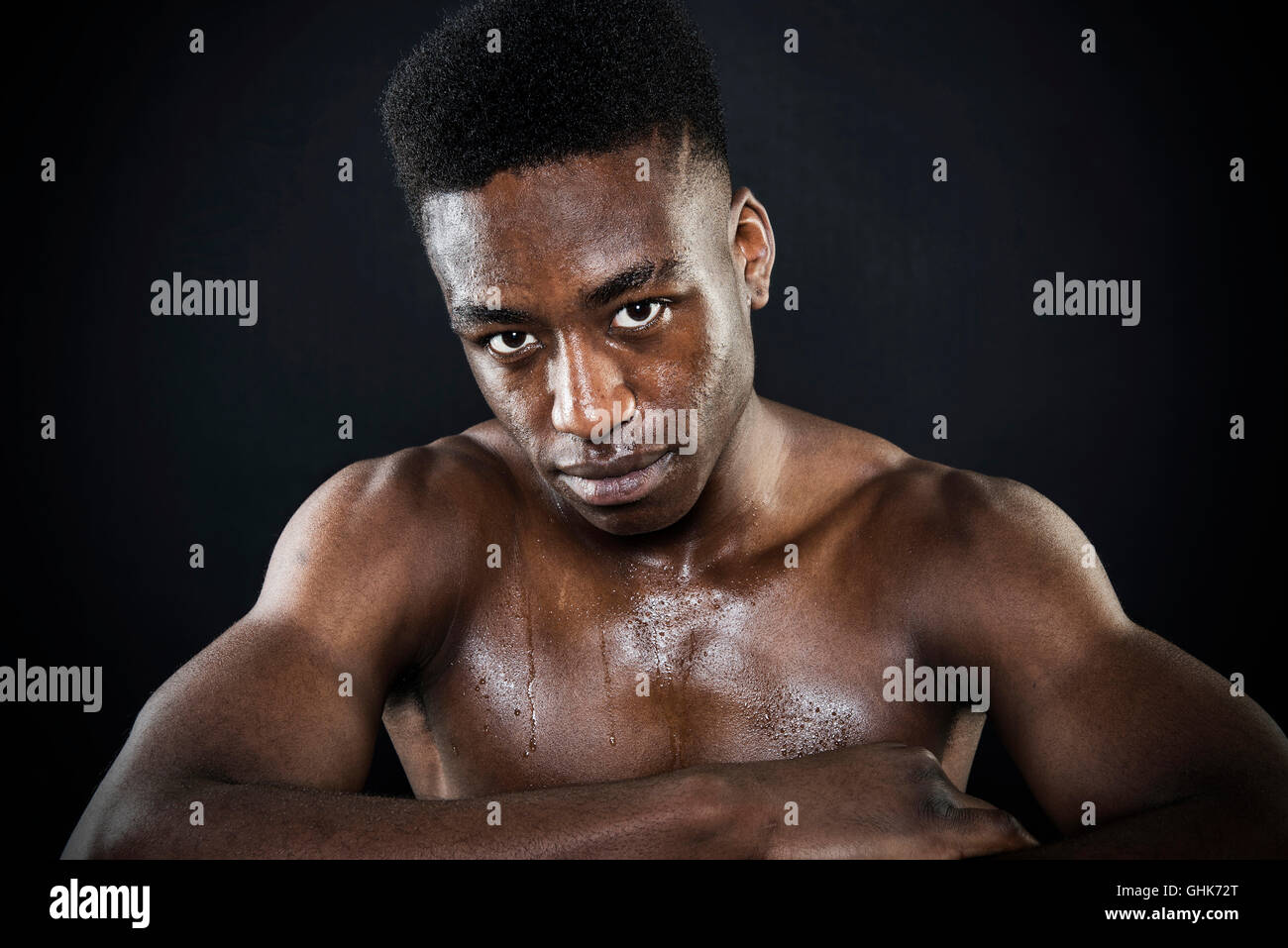 Sportsman athlete  muscular sweating wet face and torso after exercise arms folded  portrait intense look isolated - Stock Image