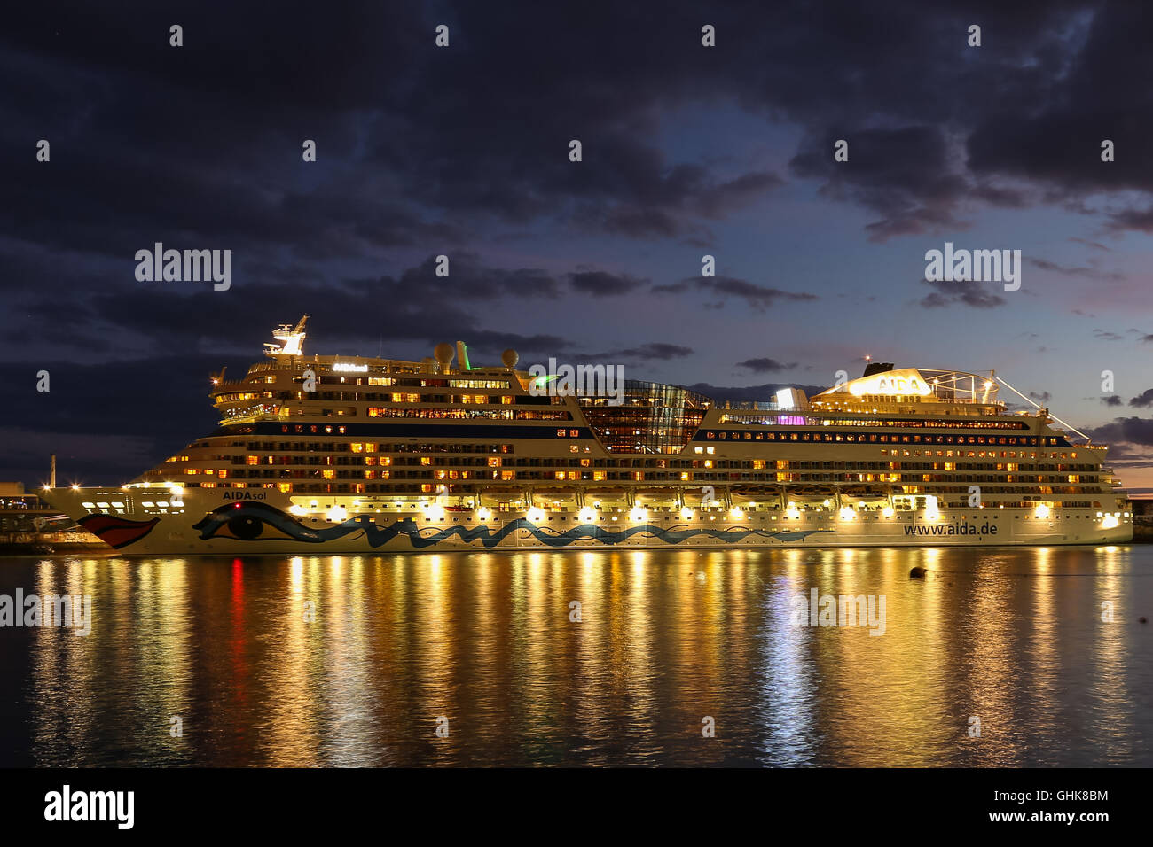 AIDA cruiseship moored in Funchal harbor at night against a sunset sky on the island Madeira - Stock Image