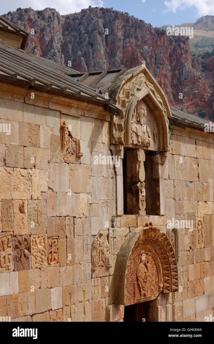 view of Mother of God church Noravank s Armenia, carving above door, with mountain setting behind, showing same - Stock Image