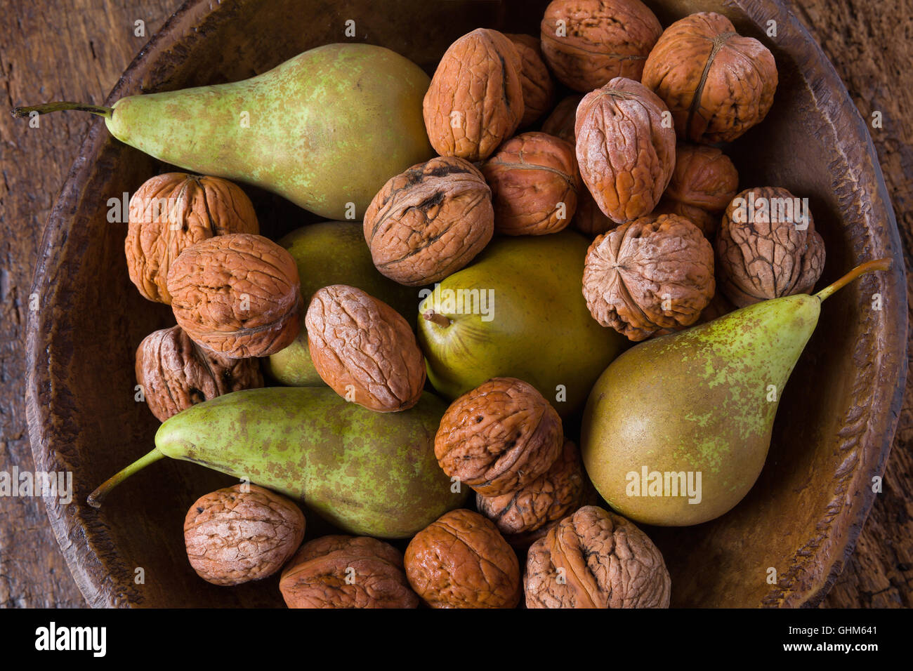 Autumn still life of fall leaves and walnuts on a grunge wooden background - Stock Image