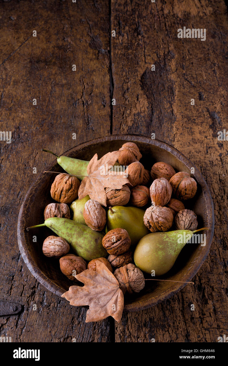 Fall still life with a bowl of pears and walnuts on a grunge wooden background - Stock Image