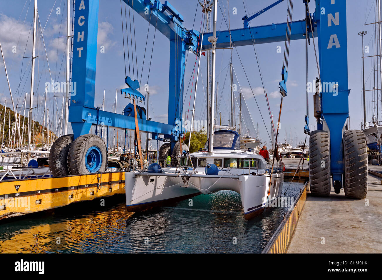 Catamaran being lifted or launched by yacht crane. - Stock Image
