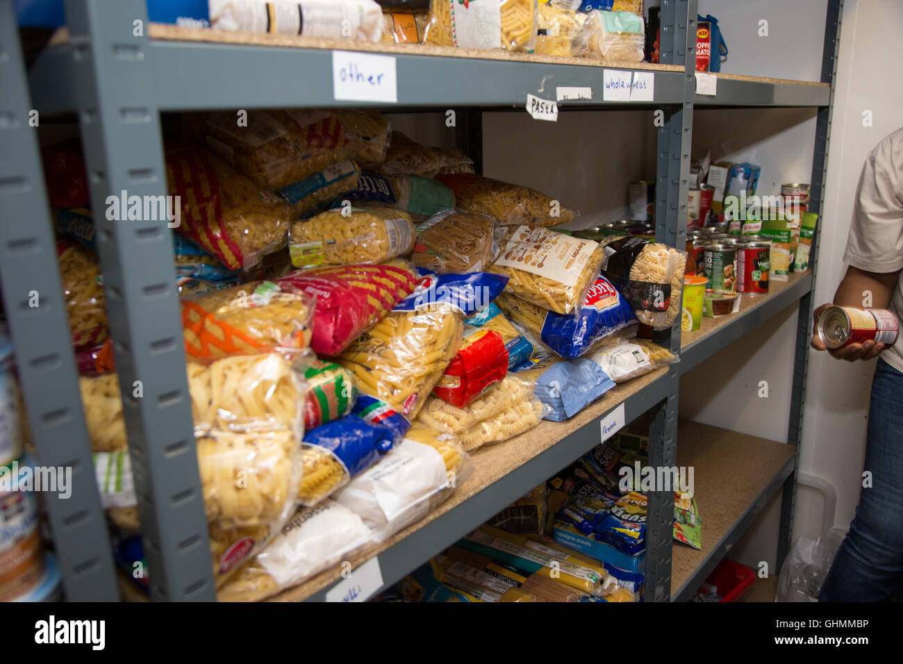 Dried pasta and cans of soup on a shelf at the North Paddington Foodbank, London - Stock Image