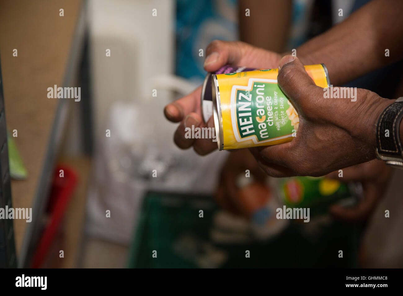 A man collecting a tin of macaroni cheese from a shelf at the North Paddington Foodbank, London - Stock Image
