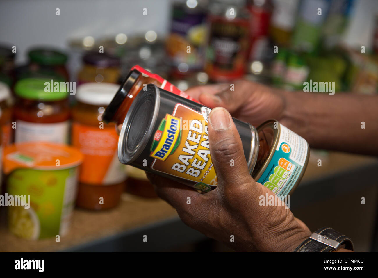 A man collecting a tin of baked beans from a shelf at the North Paddington Foodbank, London - Stock Image