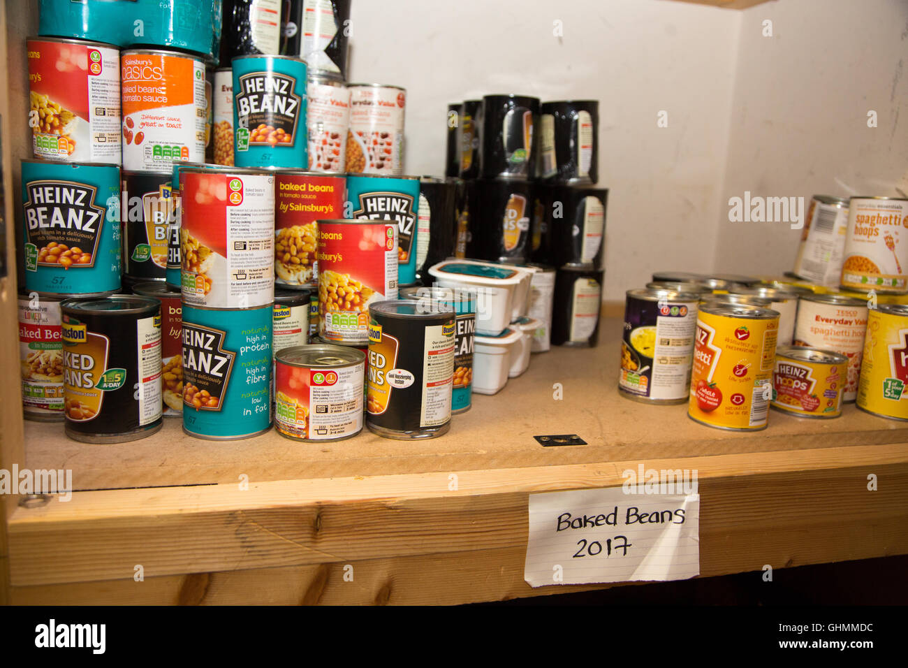 Tins of baked beans and spaghetti on a shelf at North Paddington foodbank - Stock Image