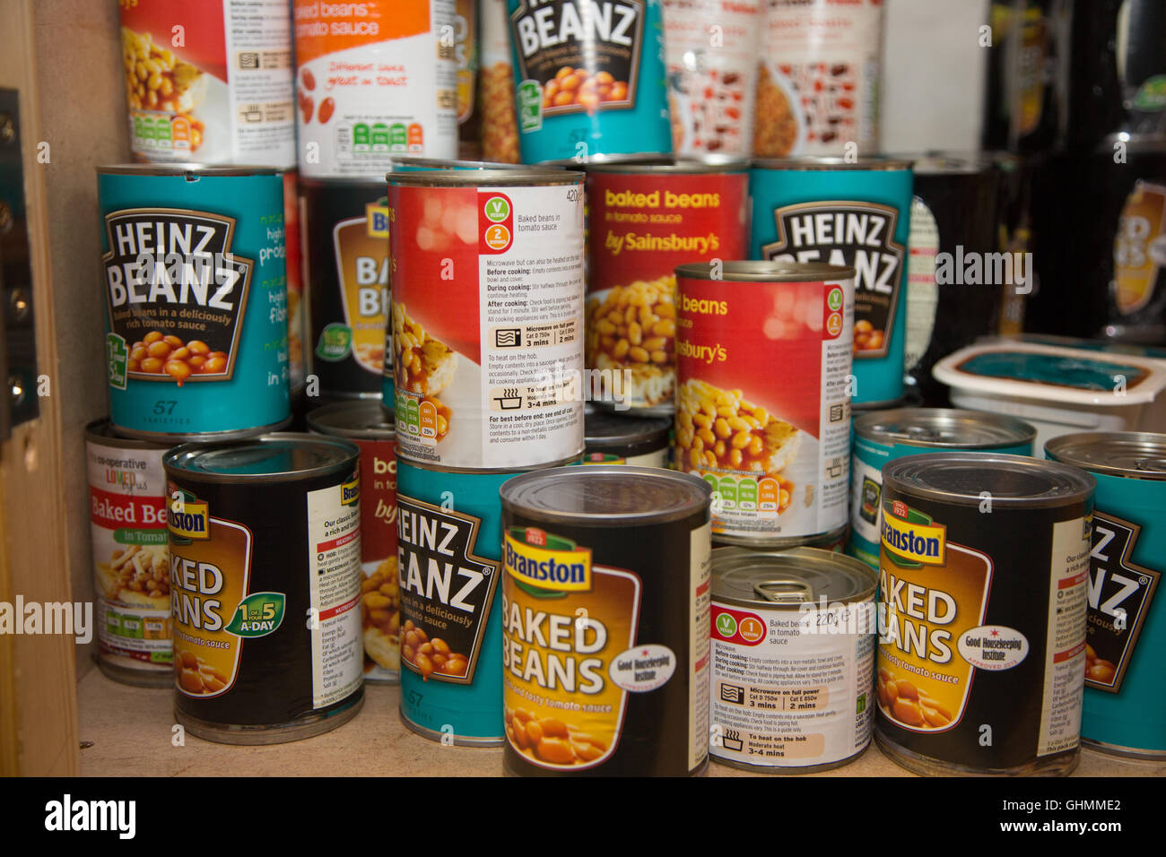 Tins of baked beans on a shelf at North Paddington foodbank waiting collection or distribution - Stock Image
