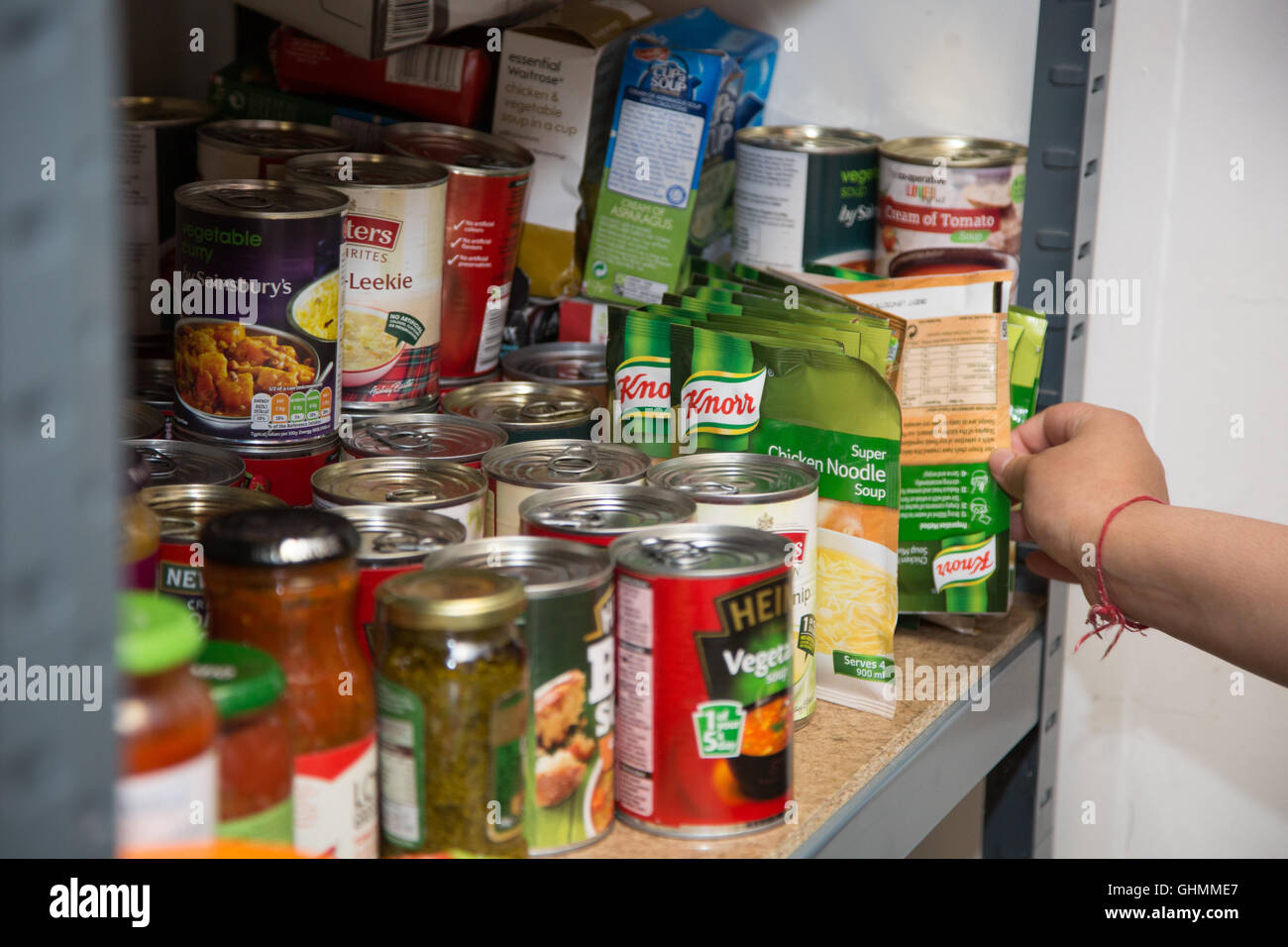 A hand reaches in to collect or stock a shelf at North Paddington foodbank. - Stock Image