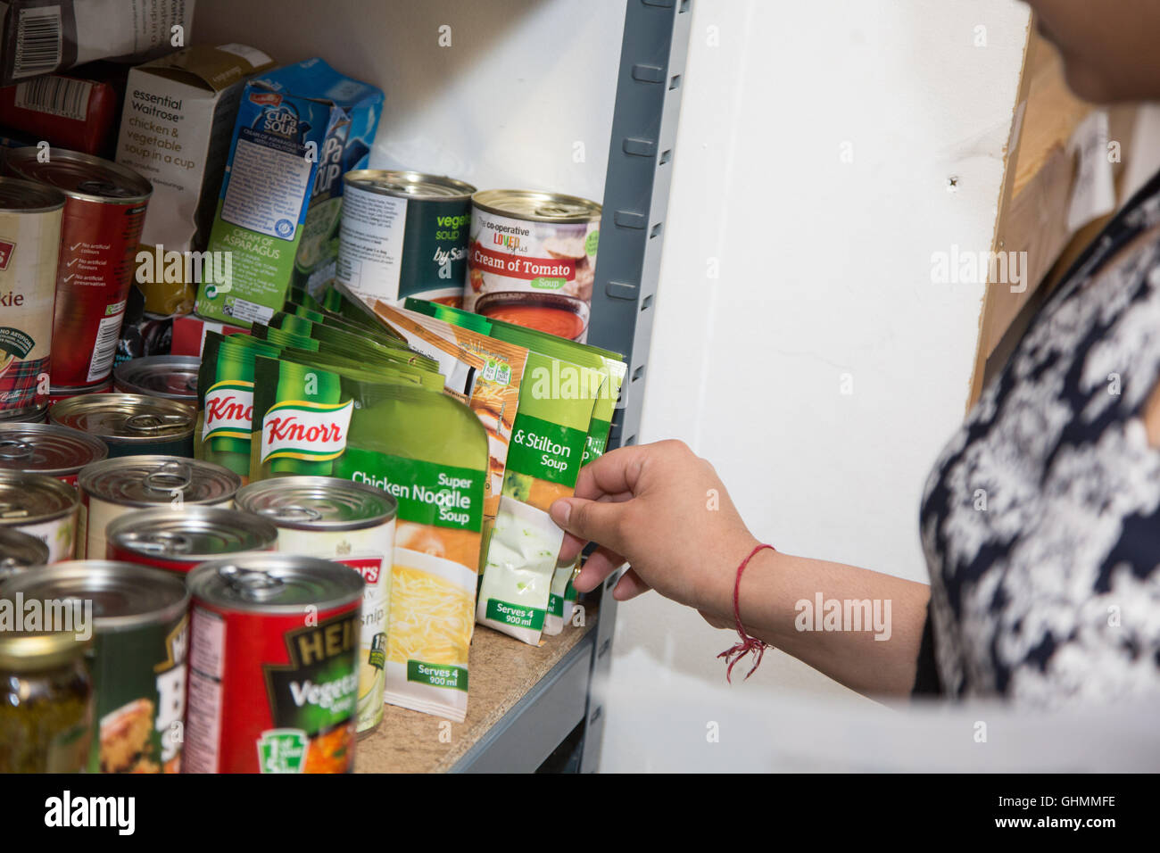 A woman's hand reaches in to collect or stock a shelf at North Paddington foodbank. - Stock Image