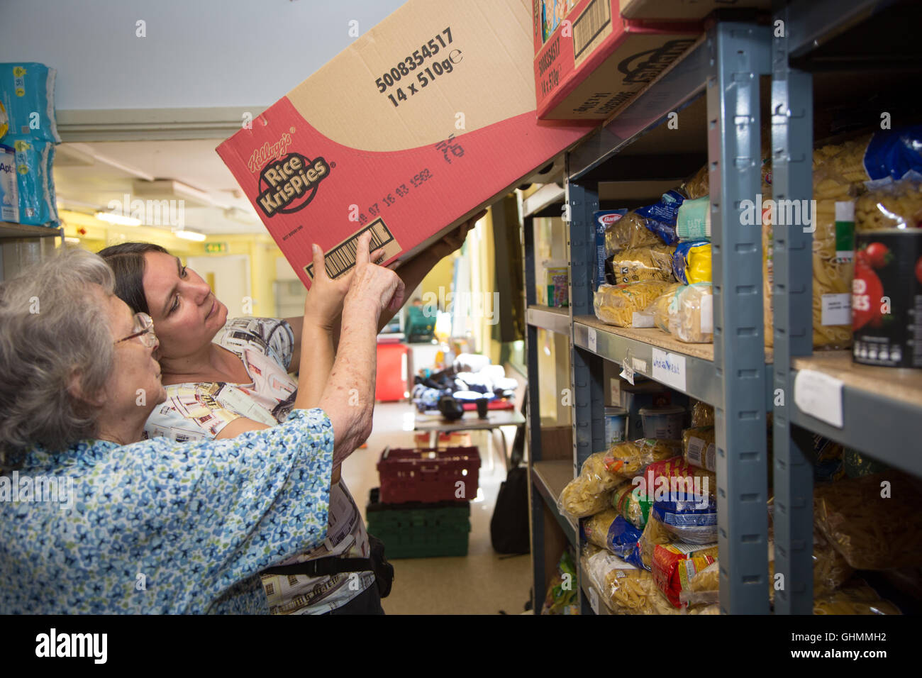 Volunteers stock shelves at North Paddington foodbank, and check sell-by dates - Stock Image