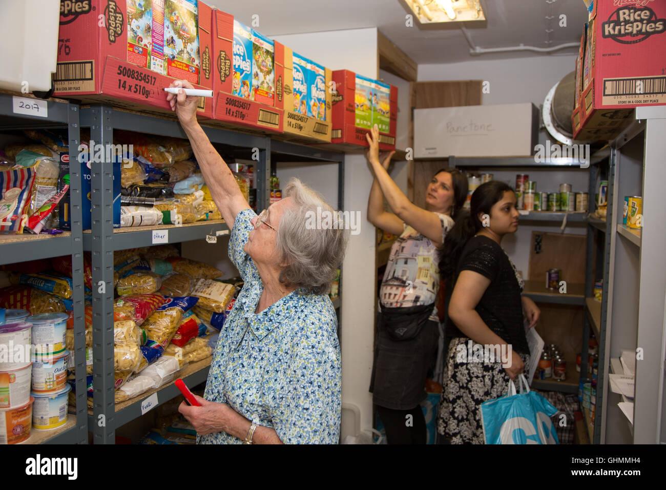 Volunteers stock shelves at North Paddington foodbank - Stock Image