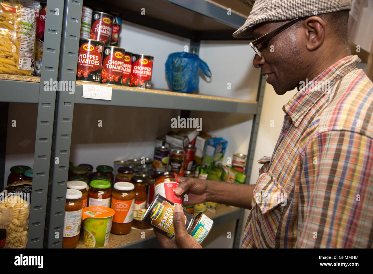 A volunteer reaches in to stock a shelf at North Paddington foodbank. - Stock Image